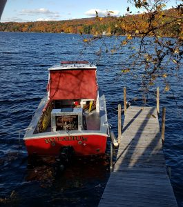 Boat in water at dock with fall colors in the background on the shore