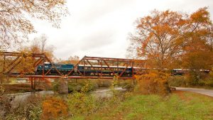 Train crossing bridge with fall colored trees in the background